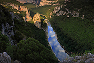 """A view at sunset of the Ardeche river and its gorges, which are actually a wonderful canyon - 35 kms long and 250 meters deep - the river dug for million years in a limestone plateau.  This part of the gorges is placed at about half lenght of the canyon and its main feature is the rock formation visible on the left of the river, know as """"La Cathédrale"""" for its vertical, sharp """"spires"""". Just to give a sense of scale of this scene, the Cathedral is about 80 meters tall, and I took this picture from a natural balcony at about 200 mts above the river bed. The slice of sky reflected in the river is so sharp and striking, that it almost looks like a rift in the Earth that let one look out to the other side of the planet. Here's where the title come from.  This is a stitch of four verticals."""