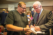 23 AUGUST 2012 - PEORIA, AZ:  Senator JOHN McCAIN (R-AZ), RIGHT, signs a book after a town hall meeting in Peoria, AZ. Sen. McCain held a town hall in Peoria, a suburb of Phoenix, to talk about the impact that sequestration would have on the Arizona economy and the Department of Defense. McCain said sequestration would immediately cost Arizona more than 35,000 defence related jobs and decimate the armed forces. Sequestration would result in about $1.2 trillion being cut from the federal budget. Sequestration, and automatic budget cuts, is scheduled to go into effect on Jan 1, 2013, if the President and Congress can't agree on budget.     PHOTO BY JACK KURTZ