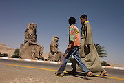 Young Egyptian boys walks past the ancient Egyptian Colossi of Memnon site, Luxor, Nile Valley, Egypt. The Colossi of Memnon (memorial temple of Amenophis III) are two massive stone statues of Pharaoh Amenhotep III, who reigned during Dynasty XVIII. For the past 3,400 years (since 1350 BC) they have stood in the Theban necropolis, west of the River Nile from the modern city of Luxor.