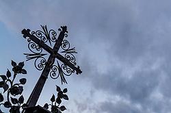 THEMENBILD - die Silhouette eines Kruzifixes auf einem Grabstein gegen den mit Wolken verhangenen Himmel fotografiert. Am 1. November, gedenken Katholiken aller Menschen, die in der Kirche als Heilige verehrt werden. Das Fest Allerseelen am darauf folgenden 2. November, ist dem Gedaechtnis aller Verstorbenen gewidmet, aufgenommen am 30.10.2016, Kaprun, Oesterreich // The silhouette of a crucifix on a gravestone photographed against the cloudy sky, on All Saints' Day 1st November, Catholics remember all people who are venerated as saints in the church. The festival Souls on the following second November is dedicated to the memory of all deceased, taken at the cemetery in Kaprun, Austria on 2016/10/30. EXPA Pictures © 2016, PhotoCredit: EXPA/ JFK