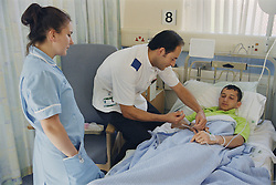 Student nurse watching staff nurse give young patient intravenous antibiotics,