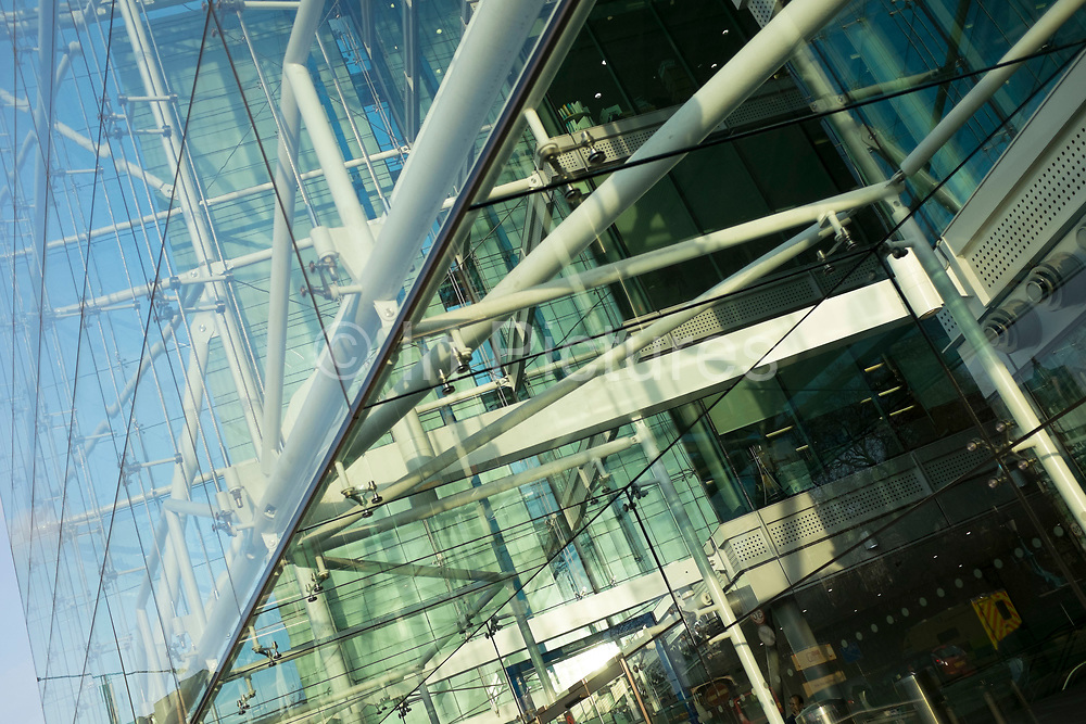 Reflections in a modern glass building. This architecture example is of a building on Tower Bridge Approach, London. The frontage is made of steel and tension cables in an ordered grid.