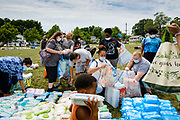 """19 JULY 2020 - DES MOINES, IOWA: People pick up baby wipes during """"A Celebration of Black Motherhood"""" in Des Moines Sunday. The event was organized by the Supply Hive and Black Lives Matter. Items were donated by members of the community and redistributed to at risk families. They distributed diapers, sanitary products, clothes, books, and toys. They had enough material to help 200 families.         PHOTO BY JACK KURTZ"""