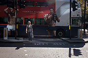 A lady is about to cross the road with macho men models in a Tommy Hilfiger bus ad behind, in the City of London. About to walk out and cross the road in the heart of the capital's financial district (founded by the Romans in the 1st Century) the woman stands in a pool sunlight unaware of the adverts behind her. We see the ripples of abdominal muscles on the torsos of two men, seemingly drying themselves with branded towels - the epitome of male sexuality and sex-appeal that helps sell lifestyle products.