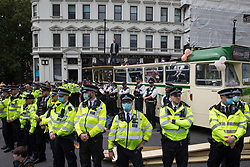 London, UK. 31st August, 2021. Metropolitan Police officers form a cordon around environmental activists from Extinction Rebellion who used a bus to block a road junction to the south of London Bridge on the ninth day of their Impossible Rebellion protests. Extinction Rebellion are calling on the UK government to cease all new fossil fuel investment with immediate effect.