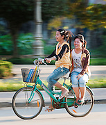 Local people cycling through the streets of Siem Reap, Cambodia