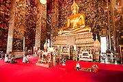 08 OCTOBER 2009 -- BANGKOK, THAILAND: People pray in the main chapel in Wat Suthat. Wat Suthat, in Bangkok, Thailand, is one of the most important Buddhist temples in Thailand. Parts of it were made Thai King Rama II. It features both the largest odination hall and largest main chapel of any Buddhist temple in Thailand. The chapel also has the largest surviving Sukothai period bronze cast statue of the Buddha.   Photo By Jack Kurtz