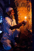 """27th August 2015, New Delhi, India.  A man who watches over peoples shoes while they pray holds a candle in the catacombs of Feroz Shah Kotla in New Delhi, India on the 27th August  2015<br /> <br /> PHOTOGRAPH BY AND COPYRIGHT OF SIMON DE TREY-WHITE a photographer in delhi<br /> + 91 98103 99809. Email: simon@simondetreywhite.com<br /> <br /> People have been coming to Firoz Shah Kotla to pray to and leave written notes and offerings for Djinns in the hopes of getting wishes granted since the late 1970's. Jinn, jann or djinn are supernatural creatures in Islamic mythology as well as pre-Islamic Arabian mythology. They are mentioned frequently in the Quran  and other Islamic texts and inhabit an unseen world called Djinnestan. In Islamic theology jinn are said to be creatures with free will, made from smokeless fire by Allah as humans were made of clay, among other things. According to the Quran, jinn have free will, and Iblīs abused this freedom in front of Allah by refusing to bow to Adam when Allah ordered angels and jinn to do so. For disobeying Allah, Iblīs was expelled from Paradise and called """"Shayṭān"""" (Satan).They are usually invisible to humans, but humans do appear clearly to jinn, as they can possess them. Like humans, jinn will also be judged on the Day of Judgment and will be sent to Paradise or Hell according to their deeds. Feroz Shah Tughlaq (r. 1351–88), the Sultan of Delhi, established the fortified city of Ferozabad in 1354, as the new capital of the Delhi Sultanate, and included in it the site of the present Feroz Shah Kotla. Kotla literally means fortress or citadel."""