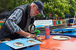 Little Venice, London, April 30th 2017. Narrowboaters from all over the uK gather for the annual Canalway Cavalcade, held on the May Day Bank holiday weekend, organised by the Inland Waterways Association, where boaters get the chance to display their immaculately prepared and brightly painted craft as well as compete in various manoeuvring tests. PICTURED: A narrow boater polishes the brasswork on his boat.<br /> Credit: ©Paul Davey<br /> To licence contact: <br /> Mobile: +44 (0) 7966 016 296<br /> Email: paul@pauldaveycreative.co.uk<br /> Twitter: @pauldaveycreate