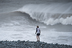 """© London News Pictures. 08/02/2014. Aberystwyth, UK. <br /> A runner watches gale force winds and big waves begin to strike the seafront at Aberystwyth on the west wales coast.  The winds are forecast to strengthen throughout the day, gusting up to 70 or 80 mph, and with the rising tide, their impact could be potentially damaging again. An amber """"be prepared"""" warning  has been issued by the Met Office for wind,. Photo credit: Keith Morris/LNP"""