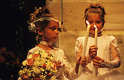 Manouche young catholic girls. holding candles, awaiting their christenings in the church.<br /><br />Europe, France, Camargue, Saintes Maries de la Mer. Gypsies praying inside the church and crypt, to their patron Saint Sara and to the Saintes Maries. Marie Jacobe and Marie Salome. Catholic gypsies come from all over Europe to celebrate this festival in mid-May every year. There are many masses, christenings and private prayers during the gypsy pilgrimmage.