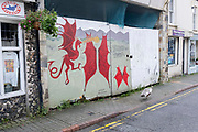 A Pea Hen struts past a hoarding featuring the image of the Welsh Dragon, on 3rd October 2021, in Bangor, Gwynedd, Wales.