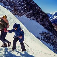 A Sherpa guide helps an elderly trekker over the 5420m Cho La pass in the Khumbu region of Nepal. 1980
