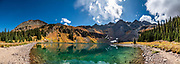 Mt Sneffels (left) and Dallas Peak (right) rise above Lower Blue Lake. Blue Lakes Trail takes you into Mt Sneffels Wilderness in Uncompahgre National Forest, San Juan Mountains, near Ridgway, Colorado, USA. This image was stitched from multiple overlapping photos.
