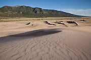 The wavy sand of the dune field tapers off into Medano Creek Basin, with the Sangre de Cristo Mountains rising in the distance, Great Sand Dunes National Park, Colorado.