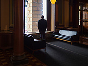 "16 MARCH 2020 - DES MOINES, IOWA: A security guard looks out a window at the State Capitol in Des Moines. Because of numerous reports of Coronavirus in Iowa, the governor is suspending the legislative session for 30 days. It was scheduled to run until mid-April. Sunday night, the Governor announced that the state health department had recorded ""community spread"" in Des Moines. As a result the State Capitol instituted mitigation measures that included mandatory health screening for everyone going into the building, canceling group tours of the building, and closing the souvenir shop and snack bar.     PHOTO BY JACK KURTZ"