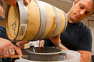 Barrel-aged cocktails made by Clyde Common's restaurant bartender, Jeffery Morgenthaler, in Portland, Oregon.  Pictured here is Jeffery and his assistant Junior Smith, straining a 3 month old barrel of Negroni, which is ripe and ready to be served.
