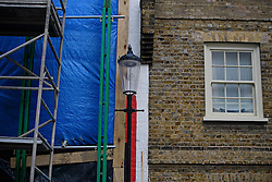 © London News Pictures. 27/04/2016. A detail showing a red strip bordering a neighbours house. A house painted with red and white stripes in the Kensington area of west London which is currently being demolished and then rebuilt. The candy stripes were originally painted on to the multi-million pound house following a dispute in which  neighbours objected to plans to demolish the building and replace it with a new house and two-storey basement. Photo credit: Ben Cawthra/LNP