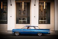 Two men in a blue 1959 Cheverlet Impala Sport Sedan  in front of the new Iberostar Hotel Packard in Havana.