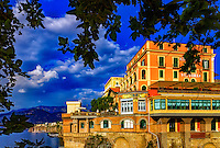 """""""The Grand Hotel Excelsior Vittoria Sorrento""""…<br /> <br /> Perched on the cliff edge of Sorrento, the inimitable Grand Hotel Excelsior Vittoria has a history full of superlatives. Owned and operated by the Fiorentino family since 1834, the property has hosted many international celebrities, who enjoyed the same breathtaking views of the Bay of Naples and Mount Vesuvius as today's guests. Ruins of Roman Emperor Augustus' villa are said to lay beneath the property, and the past is also alive in such details as the 18th-century columns, frescoed ceilings, and antiques displayed throughout. Outside, the region's beauty is evident in the lush gardens filled with Mediterranean plants, citrus and olive groves. A quick elevator ride sweeps guests from the port directly to the hotel.  Unfortunately, I was not able to stay at this historical hotel, but photographed it from across a small waterway.  The leaves of the tree I was standing under framed the hotel in its elegant splendor."""