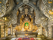 "03 APRIL 2016 - CHIANG MAI, THAILAND: The interior of the ordination hall at Wat Sri Suphan. Wat Sri Suphan is also known as the ""Silver Temple"" because of its silver ubosot, or ordination hall. The temple is more than 500 years old but the silver ordination hall was recently remodeled. The ordination hall is covered in silver and the interior is completely done in silver and gold. It's traditionally served as the main temple for the silversmiths of Chiang Mai, whose community is around the temple.     PHOTO BY JACK KURTZ"