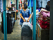 12 JANUARY 2017 - BANGKOK, THAILAND: A vendor pulls a bag clothes to her shop in Bo Bae Market. Bo Bae Market is a sprawling wholesale clothing market in Bangkok. There are reportedly more than 1,200 stalls selling clothes made in Thailand and neighboring countries. Bangkok officials have threatened to shut down parts of Bo Bae market, but so far it has escaped the fate of the other street markets that have been shut down.         PHOTO BY JACK KURTZ