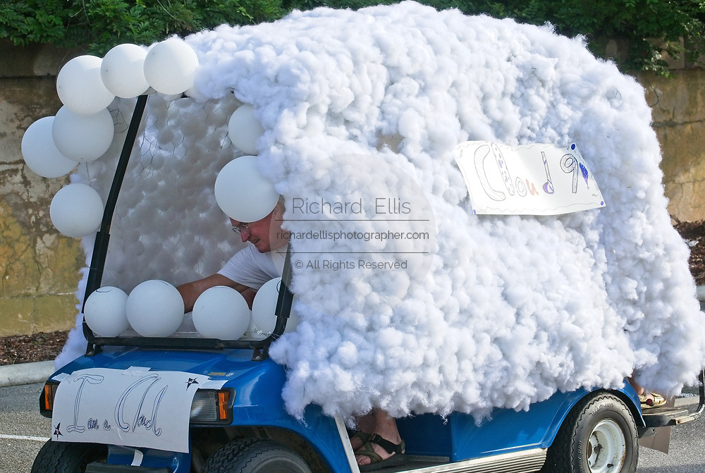 """A man arranges balloons on his """"Cloud 9"""" decorated golf cart during the annual Sullivan's Island Independence Day parade July 4, 2017 in Sullivan's Island, South Carolina. The tiny affluent sea island hosts a bicycle and golf cart parade through the historic village."""