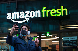 "© Licensed to London News Pictures. 16/03/2021. LONDON, UK. A customer takes a selfie outside the new 2,500 sq ft Amazon Fresh store in Wembley Park, west London on its opening day. It is the second ""just walk out"" grocery store in the UK after the opening of the Wembley branch.  As a ""contactless"" shop, it is available to anyone signed up to Amazon and with the app on their smartphone.  In-store cameras and artificial intelligence monitor customers picking up items who simply walk out and billing takes place later automatically.  Photo credit: Stephen Chung/LNP"