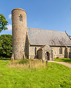 Gravestones in churchyard round tower of church of St John the Baptist, Lound, Suffolk, England,