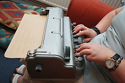 Woman with visual impairment at home typing using braille typewriter.