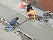 Construction workers repairing the street after having opened the street to put some utility piping in the ground.