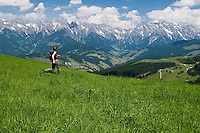 Yound adult female hikes though green grass of Alpine meadow in Austrian Alps