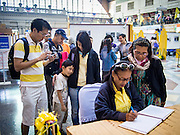 """05 DECEMBER 2013 - BANGKOK, THAILAND:  People sign a book sending birthday greetings to Bhumibol Adulyadej, the King of Thailand, at Hua Lamphong Train Station in Bangkok on the  King's 86th birthday. Dec. 5, the King's Birthday, is a national holiday in Thailand, and is also celebrated as the country's """"Fathers' Day."""" The State Railways of Thailand put on special trains to take people to the King's """"Summer Palace"""" in the oceanside community of Hua Hin where the King granted a public audience. There were also merit making ceremonies throughout the country.  Many people wear yellow on the King's Birthday because yellow is the color associated with his reign. As of 2013, he was the longest reigning monarch in the world.          PHOTO BY JACK KURTZ"""