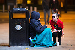 © Licensed to London News Pictures . 07/04/2017 . Manchester , UK . A woman in costume talks to a homeless woman sitting against a bin on the ground outside The Printworks on Withy Grove as a Disney themed pub crawl passes through The Printworks in Manchester City Centre . Greater Manchester Police have authorised dispersal powers and say they will ban people from the city centre for 48 hours , this evening (7th April 2017) , in order to tackle alcohol and spice abuse . Photo credit : Joel Goodman/LNP