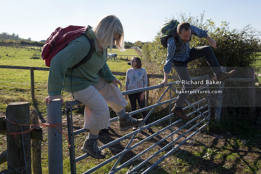 Country walkers scale a farm gate from one field to another, on 21st October 2018, near Hollingbourne, Kent, England.