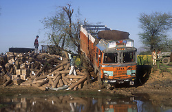Road accident in India; with lorry with large load of parcels by edge of pond,