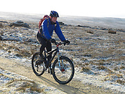 A cyclist cycles on a bridleway over the North York Moors on a frosty Winter's morning, North Yorkshire, UK