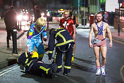 © Licensed to London News Pictures . 27/12/2017. Wigan, UK. A man dressed as a fireman takes a tumble. Revellers in Wigan enjoy Boxing Day drinks and clubbing in Wigan Wallgate . In recent years a tradition has been established in which people go out wearing fancy-dress costumes on Boxing Day night . Photo credit: Joel Goodman/LNP