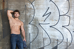 hunky man without a shirt by a graffiti wall