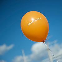 DEU, Deutschland, Germany, Stralsund, 21.09.2013:<br />Ein oranger Luftballon mit dem Schriftzug Angela Merkel vor blauem Himmel bei einer Wahlkampfveranstaltung der CDU.
