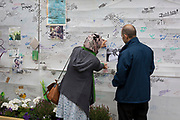 Relatives of a father killed in the Grenfell fire on the first anniversary of the tower block disaster, on 14th June 2018, in London, England. 72 people died when the tower block in the borough of Kensington & Chelsea were killed in what has been called the largest fire since WW2. The 24-storey Grenfell Tower block of public housing flats in North Kensington, West London, United Kingdom. It caused 72 deaths, out of the 293 people in the building, including 2 who escaped and died in hospital. Over 70 were injured and left traumatised. A 72-second national silence was held at midday, also observed across the country, including at government buildings, Parliament.