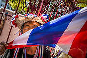 """14 JANUARY 2014 - BANGKOK, THAILAND:  A protestor kisses the Thai flag in front of Royal Thai Police headquarters. Hundreds of protestors picketed police headquarters because they accuse the police of siding with the government during the protests. Tens of thousands of Thai anti-government protestors continued to block the streets of Bangkok Tuesday to shut down the Thai capitol. The protest, """"Shutdown Bangkok,"""" is expected to last at least a week. Shutdown Bangkok is organized by People's Democratic Reform Committee (PRDC). It's a continuation of protests that started in early November. There have been shootings almost every night at different protests sites around Bangkok, but so far Shutdown Bangkok has been peaceful. The malls in Bangkok are still open but many other businesses are closed and mass transit is swamped with both protestors and people who had to use mass transit because the roads were blocked.    PHOTO BY JACK KURTZ"""