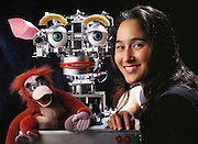 """Kismet is a complex autonomous, stationary robot developed by Dr. Cynthia Breazeal, at the time of this image a doctoral studies student at the MIT Artificial Intelligence Lab under the direction of Rod Brooks. Breazeal's immediate goal for Kismet is to replicate and possibly recognize human emotional states as exhibited in facial expressions. Kismet's eyelids, eyebrows, ears, mouth, and lips are all able to move independently to generate different expressions of emotional states. In this photograph, Cynthia poses with Kismet and """"King Louie"""", a toy often used to stimulate the robot."""