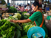 30 DECEMBER 2015 - BANGKOK, THAILAND:  An produce vendor sets up her market stall in Bang Chak Market. The market is supposed to close permanently on Dec 31, 2015. The Bang Chak Market serves the community around Sois 91-97 on Sukhumvit Road in the Bangkok suburbs. About half of the market has been torn down. Bangkok city authorities put up notices in late November that the market would be closed by January 1, 2016 and redevelopment would start shortly after that. Market vendors said condominiums are being built on the land.           PHOTO BY JACK KURTZ