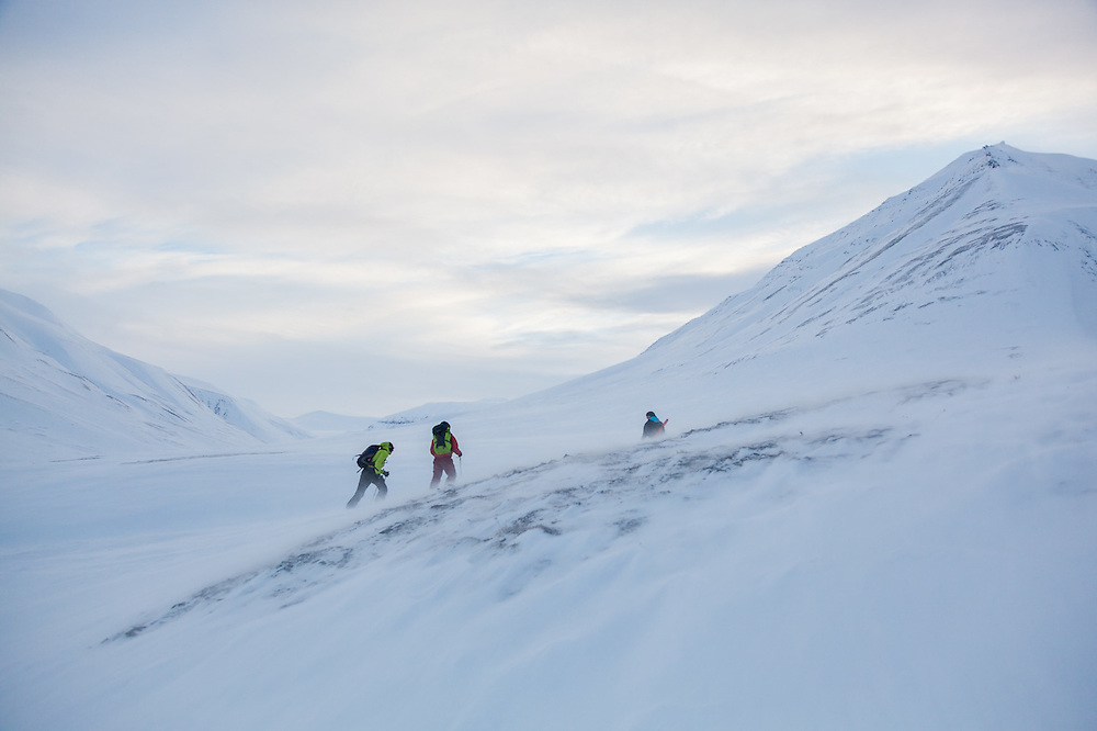 Nate Stevens, Michelle Blade, and Kiya Riverman climb up agains the wind in Foxdalen, Svalbard.