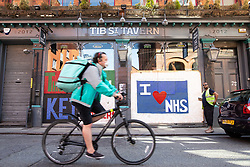 © Licensed to London News Pictures . 20/05/2020 . Manchester , UK . A Deliveroo cyclist wearing a face mask cycles past boarded up windows at the Tib Street Tavern , which feature murals in support of the NHS . On the hottest day of the year so far independently run coffee shops and bars are open and trading with social distancing measures applied , after a period of being shut in an effort to reduce the spread of Covid-19 . Photo credit : Joel Goodman/LNP