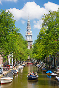 Zuiderkerk in Old Town and tourist boat taking tour cruise group sightseeing on Dutch canals, Groenburgwal, Amsterdam, Holland