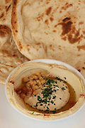 A serving of Humus, tahini, Olive oil, Parsley and pita