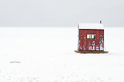 Red ice fishing hut in snowstorm