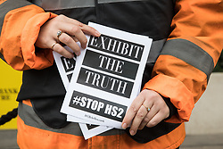 An activist dressed as a HS2 worker poses with a leaflet reading Exhibit The Truth: Stop HS2 during a HS2 Chainsaw Massacre protest outside the Among The Trees exhibition at the Hayward Gallery on 30 October 2020 in London, United Kingdom. The protest was intended to highlight both the daily environmental destruction being wrought for the controversial HS2 high-speed rail project and instances of violence and brutality by security guards and bailiffs working on behalf of HS2 Ltd.